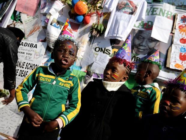 Alunos desejam feliz aniversário ao ex-presidente Nelson Mandela em frente ao hospital onde ele segue internado em Pretória (Foto: Stephane de Sakutin/AFP)