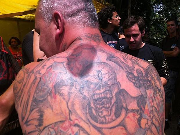 Marcos Motolo, de 40 anos, já é uma celebridade entre os fãs do Iron Maiden. Ele tem 172 tatuagens, todas com as capas e símbolos do grupo. Motolo entrou para o Guiness como o fã que tem mais tatuagens no mundo com os ideogramas da banda. A primeira tatuagem foi em 1999. Durante seis anos seguidos, ele passou 18 horas por dia desenhando a pele. Motolo veio de São Paulo para assistir ao show da banda e aguarda a abertura dos portões da Cidade do Rock, marcada para as 14h (Foto: Tássia Thum/G1)