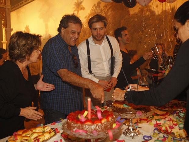 Dennis Carvalho corta o bolo (Foto: Lado a Lado/TV Globo)
