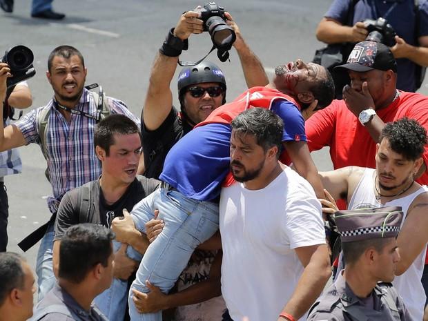 Ferido, manifestante a favor do ex-presidente Luiz Inácio Lula da Silva é levado por companheiros durante confronto com a Polícia Militar em frente ao Fórum Criminal da Barra Funda. A polícia usou de força para tentar dispersar manifestantes (Foto: Nelson Antoine/Frame/Estadão Conteúdo)