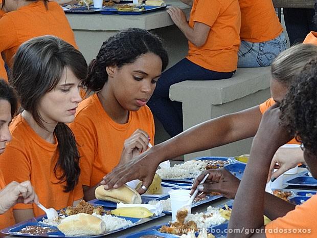 Detenta pega comida de Carolina (Foto: Guerra dos Sexos / TV Globo)