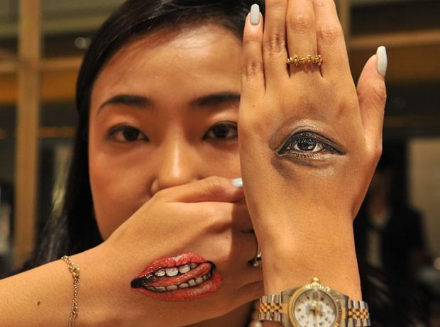 Modelo exibiu imagens superrealistas de um olho e boca nas mãos em um evento de arte em Tóquio (Foto: Yoshikazu Tsuno/AFP)