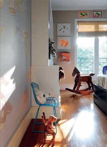 A partir da entrada, à esq., fica o adesivo de mapa-múndi produzido pela tergoprint. A cadeira Bertoia azul é da desmobilia, e o cavalinho, da Maria Jovem. Pintada num tom entre o cinza e o bege, a parede da janela tem quadros da Fast Frame (Foto: Marcelo Magnani)