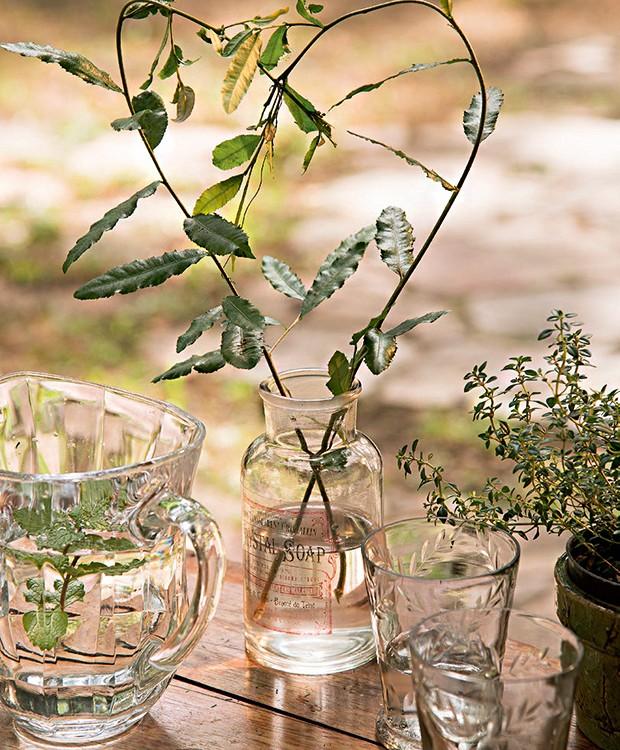 Com ajuda de um arame, galhos ganham forma de coração. Vidro de botica Id Rent Design, jarra e copos D. Filipa (Foto: Cacá Bratke/Editora Globo)