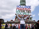 Manifestante mascarado segura cartaz com a frase &quot;Hollande agrava as divises sociais&quot;, durante protesto em Paris neste domingo (5) contra as medidas austeras do presidente francs, Franois Hollande