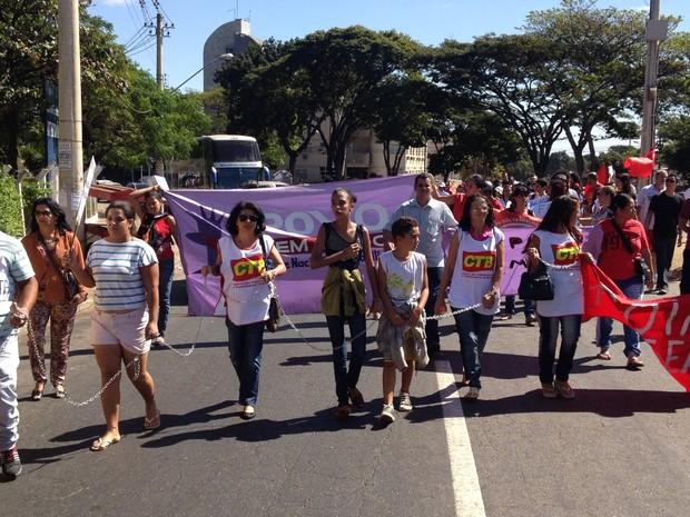 Manifestantes caminham acorrentados em ato contra Michel Temer, em Goiânia, Goiás (Foto: Vitor Santana/ G1)