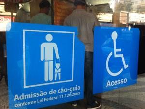 Adesivo na porta do banco fala sobre lei federal que permite acesso a cão-guia (Foto: Carolina Lauriano/G1)