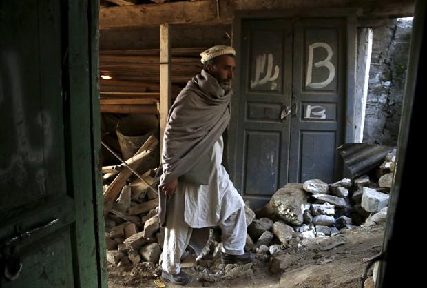 Homem caminha entre destroços de casa em Aryankoat, perto de Dir Bala, no Paquistão (Foto: Khuram Parvez /Reuters)