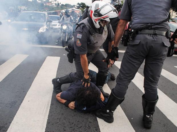 Policiais seguram manifestante no chão na rodovia Raposo Tavares, em São Paulo. Funcionários e estudantes da Universidade de São Paulo (USP) montaram barricadas bloqueando a rodovia durante protesto contra a terceirização e o ajuste fiscal (Foto: Fábio Vieira/Código 19/Estadão Conteúdo)