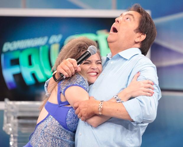 Socorro invade o palco a agarra Faustão no palco do programa (Foto: Domingão do Faustão/ TV Globo)