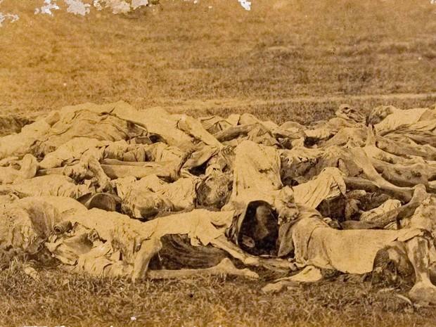Corpos de paraguaios mortos durante a guerra empilhados no campo, em imagem de 1866 (Foto: Fundação Biblioteca Nacional)