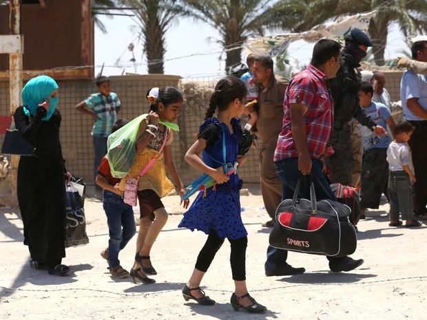 Imagem divulgada neste domingo pela AP mostra retirada em massa de moradores de Ramadi, fugindo das tropas do Estado Islâmico (Foto: Hadi Mizban/AP)