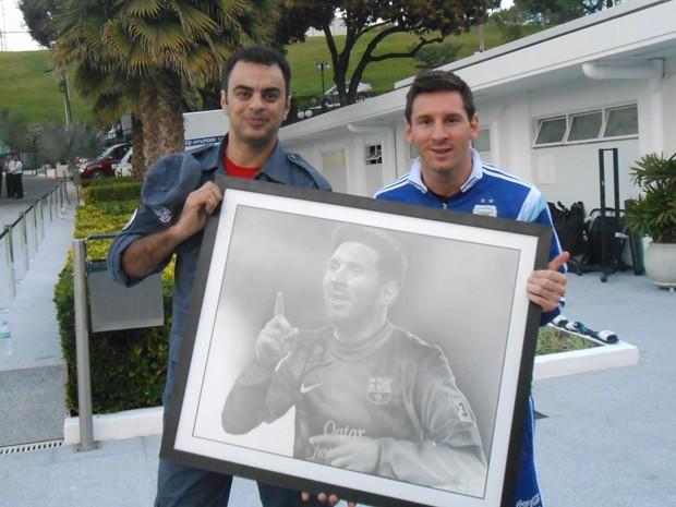 Bombeiro Alexandre Porto entrega quadro ao craque argentino Messi.  (Foto: Arquivo pessoa/ Alexandre Porto)