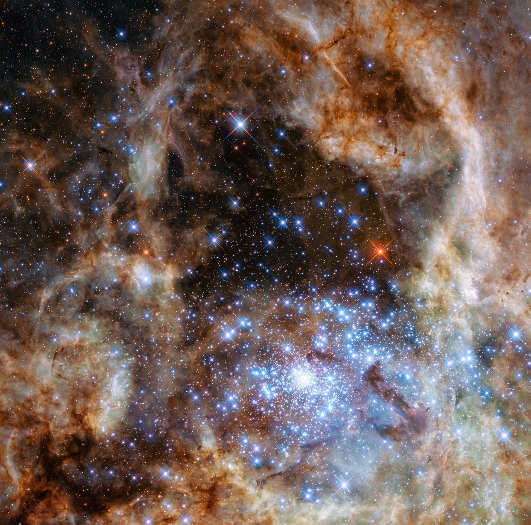 Imagem mostra a região central da Nebulosa da Tarântula na Grande Nuvem de Magalhães. o aglomerado estelar R136 pode ser visto no canto direito inferior da imagem  (Foto: NASA, ESA, P Crowther/University of Sheffield)