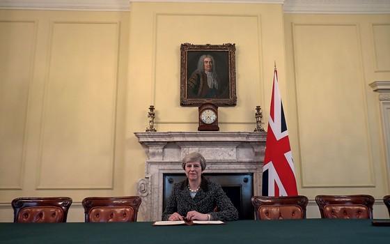 Theresa May assina a carta que dá inicio ao Brexit (Foto: Christopher Furlong// Reuters)