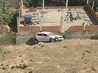 Carro cai em ribanceira na BR-381 e bate no muro de uma casa