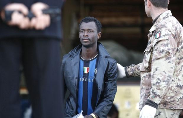 Homem é ajudado por soldado quando chega ao porto italiano de Augusta, nesta sexta-feira (21) (Foto: Antonio Parrinello/Reuters)