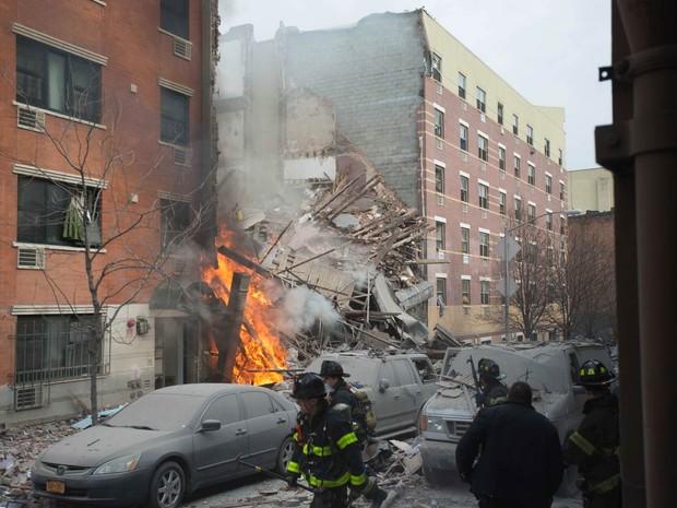 Chamas são vistas na parte da frente dos prédios desabados (Foto: Jeremy Sailing/AP)
