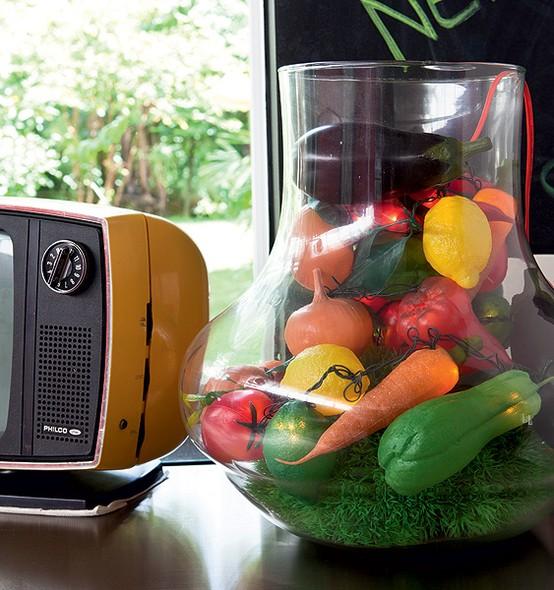 Em cima da bancada desta cozinha, um vaso de vidro guarda legumes feitos de plástico, iluminados. São réplicas divertidas de alimentos, que dão um ar de descontração ao espaço, assinadas pela estilista francesa Sylvie