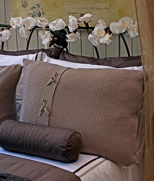Enroscadas na cabeceira de ferro, as luzinhas envoltas por flores brancas de papel crepom decoram a cabeceira da cama