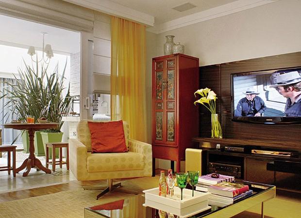 O armário chinês, R$ 2.800, da L'Oeil, faz parte do home theater, mas também serve às salas de estar e jantar. O painel de zebrano e o móvel laqueado de preto foram feitos pela Marcenaria Blanco Design. Mesa de centro e poltrona da Breton. Mesa redonda e  (Foto: Casa e Jardim)