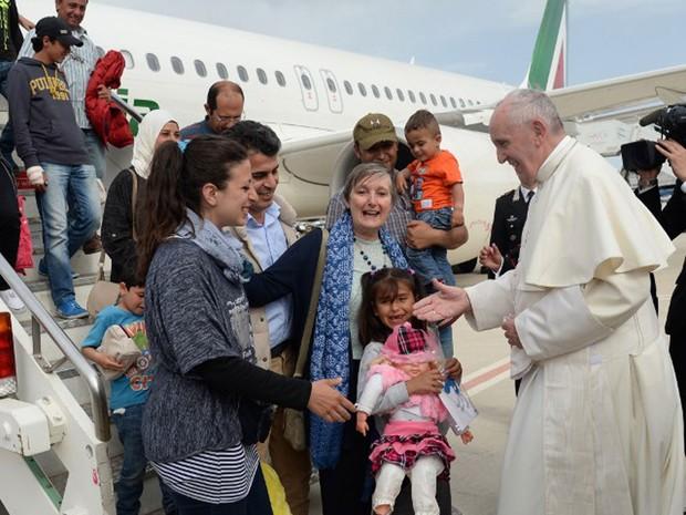 Papa Francisco dá boas-vindas ao grupo de refugiados sírios ao chegar ao Aeroporto de Ciampino, em Roma. Neste sábado, o pontífice visitou a ilha grega de Lesbos e levou um grupo para morar na Itália (Foto: Filippo Monteforte/AFP)