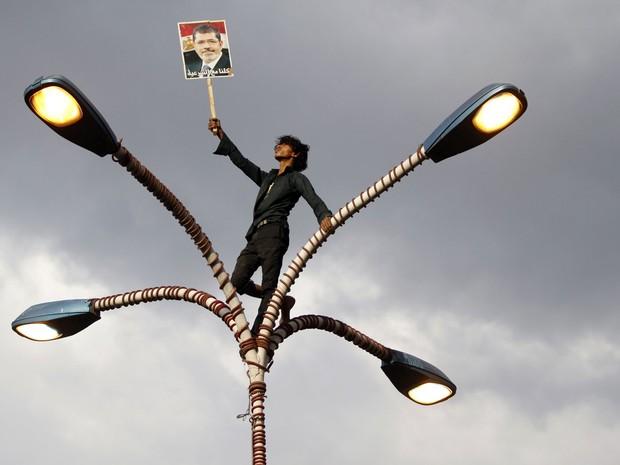 15/8 - Apoiador de Mohamed Morsi ergue uma placa com o rosto do ex-presidente deposto, equilibrando-se sobre postes de luz durante marcha em Sanaa, no Iêmen, em apoio aos manifestantes egípcios. Na placa, se lê: 'Estamos todos do lado da legitimidade' (Foto: Mohamed al-Sayaghi/Reuters)