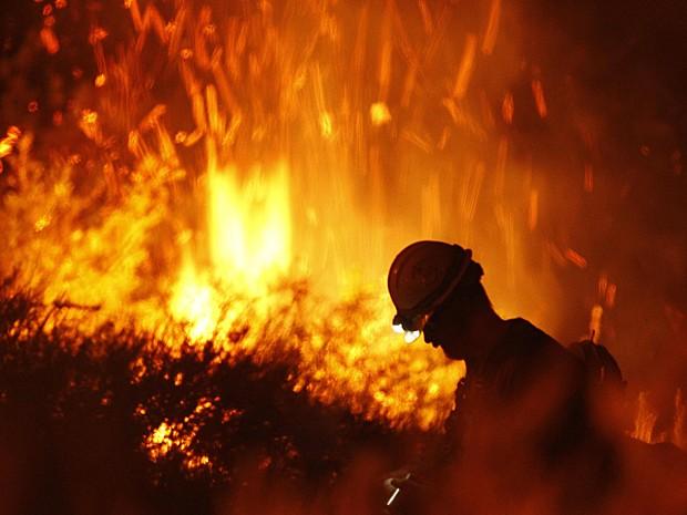 Bombeiro é visto próximo às chamas na tentative de controlar o fogo e proteger as casas na região de Newbury Park (Foto: Patrick T. Fallon/Reuters)