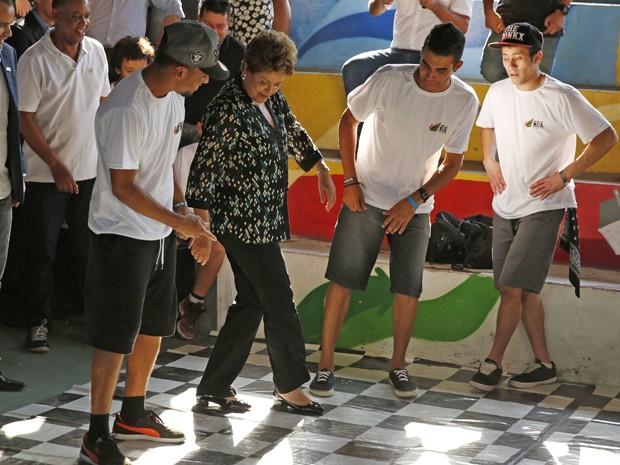 A presidente Dilma Rousseff ensaia passos de dança durante lançamento do livro 'Um País Chamado Favela', no Rio (Foto: Pilar Olivares/Reuters)