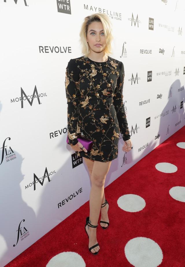 Momentos antes de tirar os sapatos, no tapete vermelho de premiação de moda (Foto: Getty Images)
