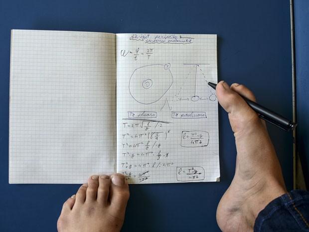 Arijon Krasniqi resolve problema de matemática usando apenas os pés (Foto: Armend Nimani/AFP)