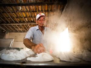 Seu Benedito coloca a massa no fogo enrolada em pano quente. (Foto: Jonathan Lins/G1)