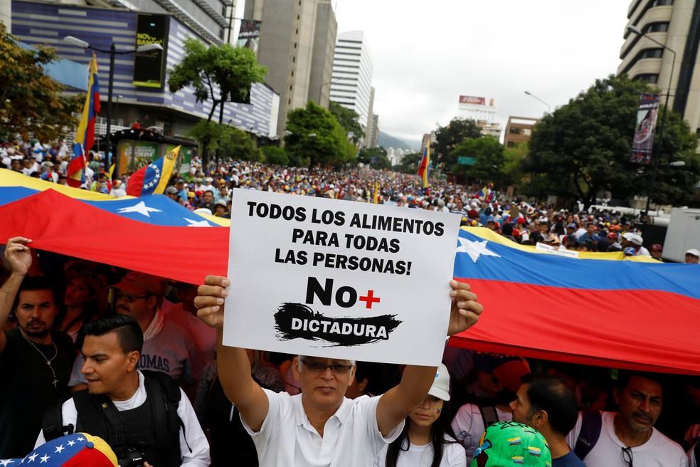 No Dia do Trabalhador, manifestantes seguram bandeira da Venezuela e cartaz onde se lê: 'Todos os alimentos para todas as pessoas! Sem mais ditadura'; protesto contra o presidente venezuelano, Nicolás Maduro, aconteceu em Caracas nesta segunda-feira, dia 1º de maio de 2017 (Foto: Carlos Garcia Rawlins/Reuters)