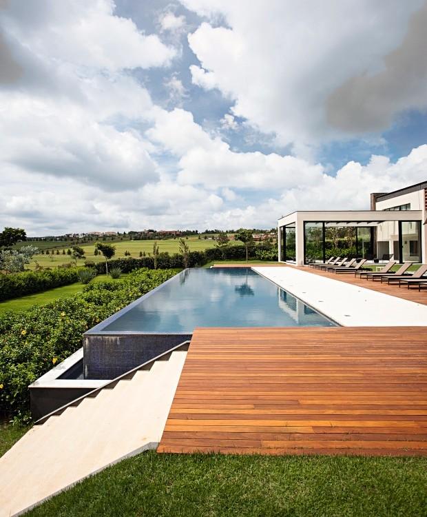 Escalonamento. A piscina com borda infinita é seguida, logo abaixo, por maciço de alamanda. O deque é de cumaru (Foto: Gui Morelli / Divulgação)