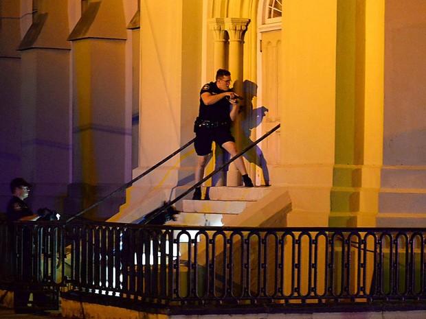 À porta da Igreja Emanuel AME, policiais procuram o suspeito de ter aberto fogo e matado fiéis em Charleston (Foto: Matthew Fortner/The Post And Courier/AP)