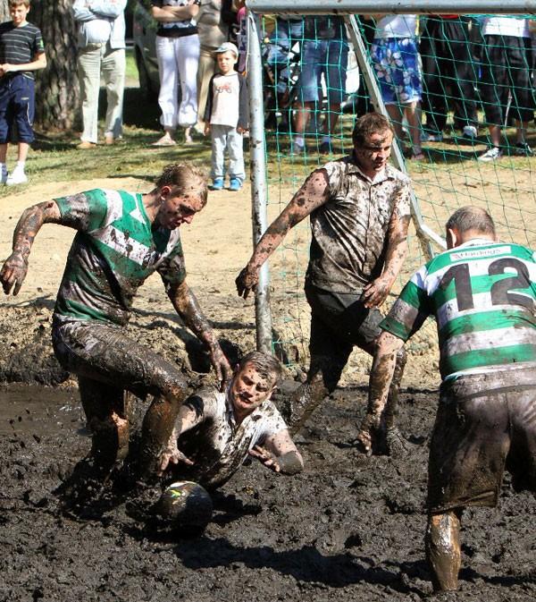 Homens jogam futebol na lama em Dia Nacional do Homem, na Lituânia. (Foto: Petras Malukas/AFP)