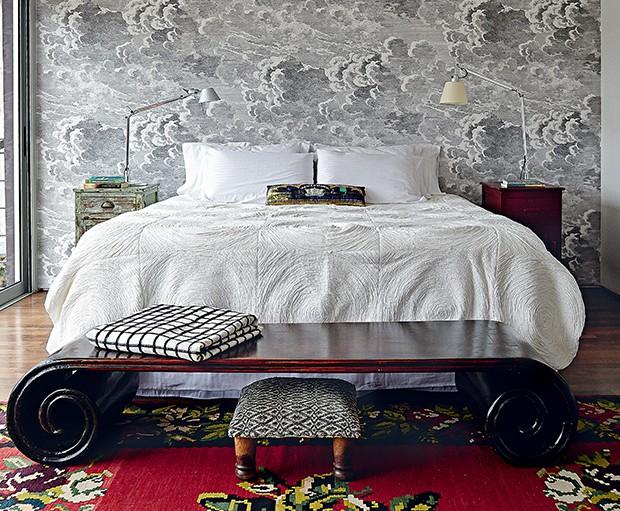 Quarto do casal | No andar superior, o cômodo tem papel de parede da Fornasetti. Aos pés da cama, peseira chinesa, da Ethnix. Tapete artesanal da Turquia. Sobre os criados- mudos, luminárias Tolomeo, da La Lampe.  (Foto: Victor Affaro)