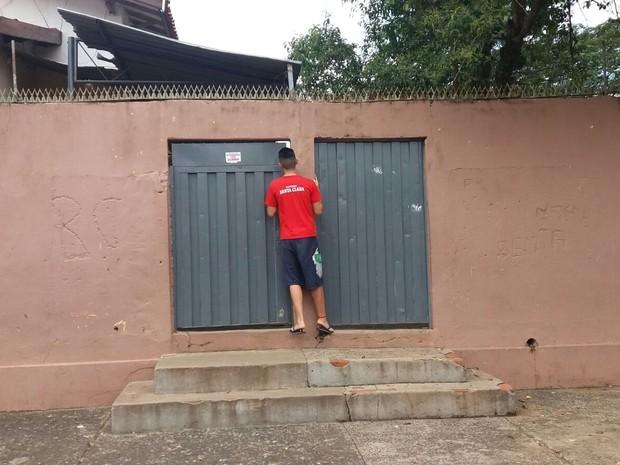 Jovem observa escola Pedro Moraes Cavalcanti pelo portão em Piracicaba (Foto: Thainara Cabral/G1)