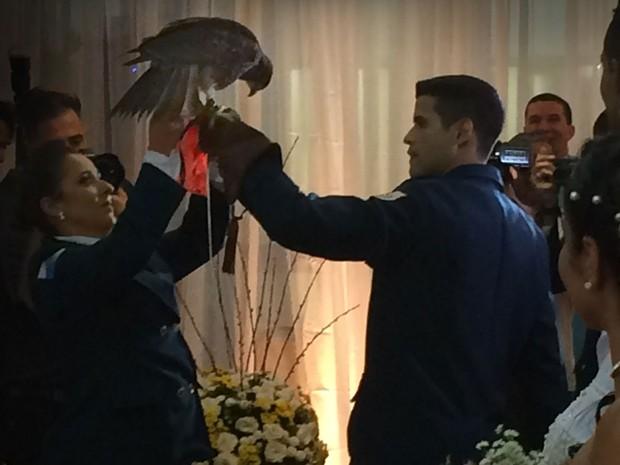 Gavião, que entrou voando pelo salão, foi o responsável pela entrega das alianças que foram trocadas pelos casais (Foto: Daniel Silveira / G1)