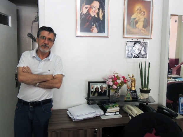 Foto da filha Jennefer ao lado de pintura de Nossa Senhora no escritório de Adherbal (Foto: Felipe Truda/G1)