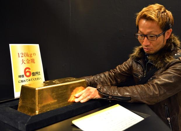 Visitante tenta levantar barra de ouro puro, pesando 120 kg  (Foto: Yoshikazu Tsuno/AFP)