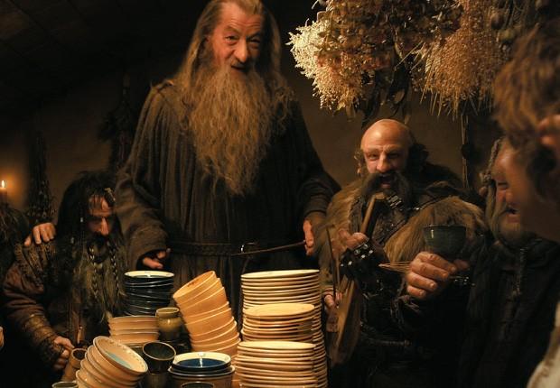 DE VOLTA À TERRA MÉDIA O mago Gandalf (Ian McKellen, em pé, à esq.) convence Bilbo (de costas, à dir.)  a ajudar um grupo de anões a recuperar seu tesouro  (Foto: divulgação)