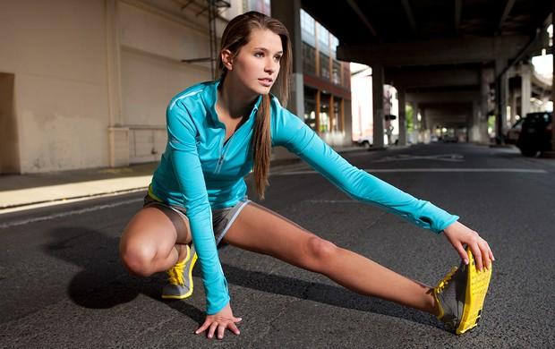 Mulher alongando antes de correr (Foto: Getty Images)