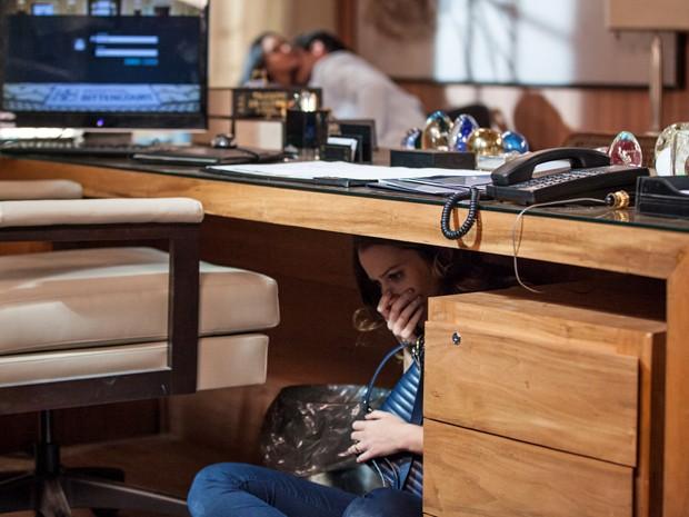 Laura se esconde embaixo da mesa enquanto Marcos e Sueli se beijam no sofá (Foto: Fabiano Battaglin/Gshow)