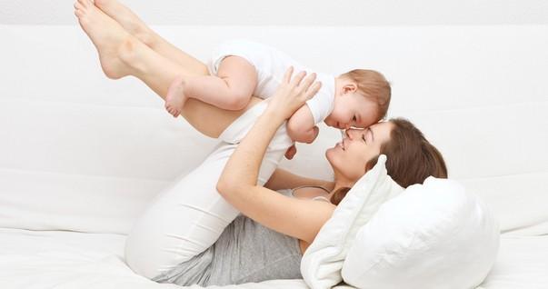 Mãe brincando com bebê no sofá (Foto: Shutterstock)