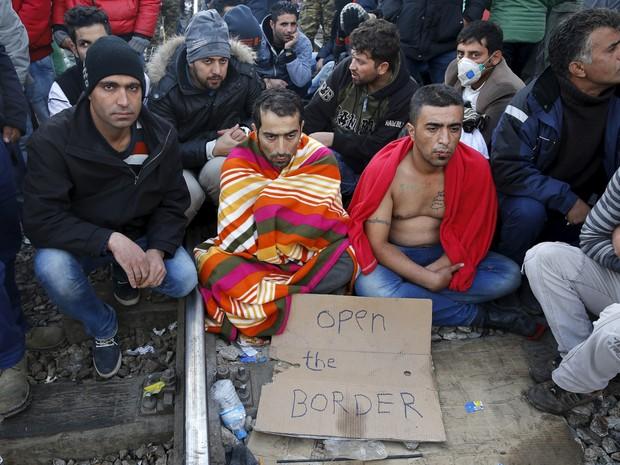 migrantes sentados nos trilhos de ferrovia na fronteira entre Grécia e Macedônia, com placa escrito 'abram a fronteira', nesta segunda-feira (23) (Foto: Yannis Behrakis/Reuters)