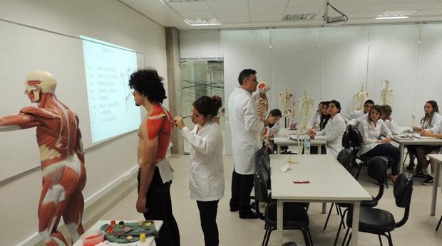 Modelo é pintado enquanto op professor explica as questões tratadas em aula (Foto: Tatiana Lopes/G1)