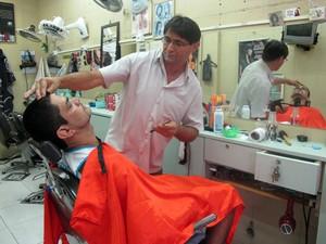Gilvan trabalha mais de 12 horas, seis vezes por semana, na barbearia na entrada da Rocinha (Foto: Tássia Thum/G1)