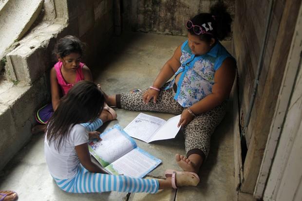 Dana Garcia, de 8 anos, lê um livro com suas amigas, que tem a mesma idade dela (Foto: Reuters/Fredy Builes)