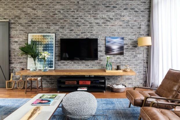 Living. A parede coberta de tijolos da Palimanan traz clima aconchegante e toque industrial à casa. À dir., fotografia trazida de Nova York. Pufe da Codex Home (Foto: Evelyn Müller / Divulgação)